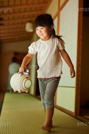 蚊取り豚を持って歩く女の子の写真素材 [FYI02060803]