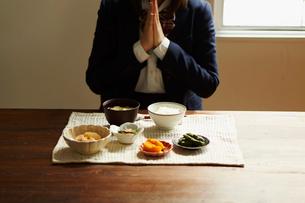 食卓で手を合わせる女子学生の写真素材 [FYI02060823]