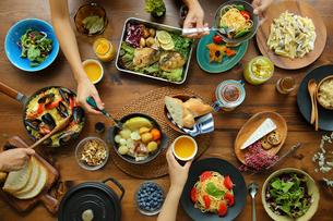 洋食がのった食卓と食事をする4人の手元の写真素材 [FYI02060835]