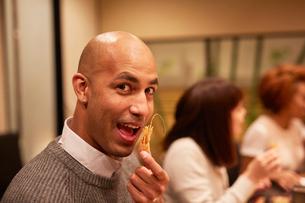 エビの頭のから揚げを食べる外国人男性の写真素材 [FYI02060845]