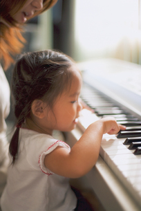 鍵盤に触る女の子の写真素材 [FYI02060850]