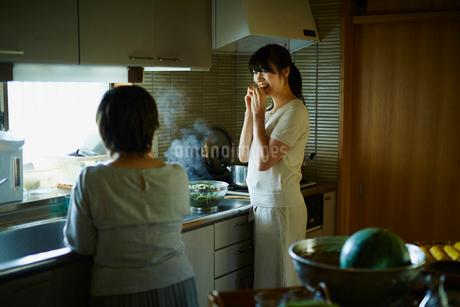 キッチンで枝豆を食べる娘と母親の写真素材 [FYI02060859]