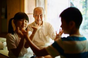 あやとりをする孫たちと笑顔の祖父の写真素材 [FYI02060885]