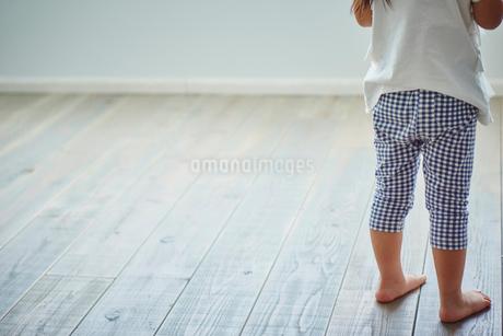 フローリングの床に立つ裸足の女の子の写真素材 [FYI02060901]