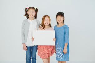 メッセージボードを持つ日本人と外国人の女の子3人の写真素材 [FYI02060946]