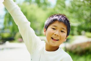 片手を上げる笑顔の男の子の写真素材 [FYI02060948]