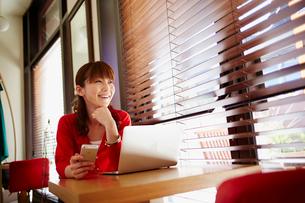 カフェでノートパソコンを開きスマートフォンを持つ女性の写真素材 [FYI02061000]