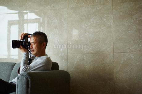 カメラを構えるミドル男性の写真素材 [FYI02061004]