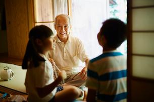 あやとりをする孫たちと笑顔の祖父の写真素材 [FYI02061011]