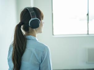 ヘッドフォンをつけたミドル女性の写真素材 [FYI02061045]
