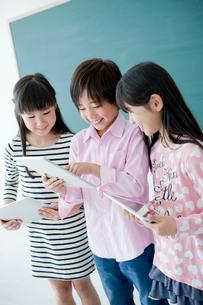 教室でタブレットPCを操作する小学生3人の写真素材 [FYI02061056]