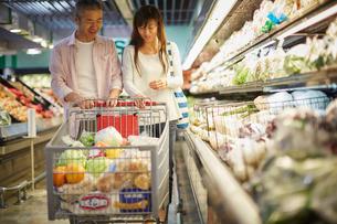スーパーマーケットで買い物をする夫婦の写真素材 [FYI02061096]