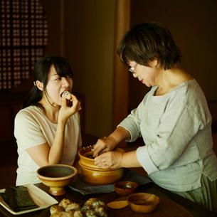 おにぎりを食べる娘と母親の写真素材 [FYI02061108]