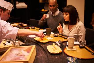 寿司屋で食事をする外国人カップルの写真素材 [FYI02061119]