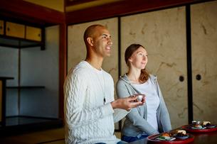 和室で日本酒を楽しむ外国人カップルの写真素材 [FYI02061135]
