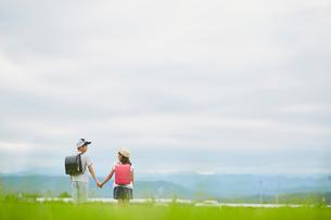 手をつなぐ小学生の兄妹と空の写真素材 [FYI02061143]