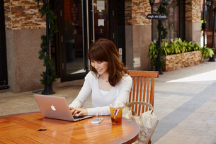 オープンカフェで仕事をする女性の写真素材 [FYI02061297]