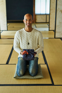 風呂敷包みを持って正座する外国人男性の写真素材 [FYI02061340]