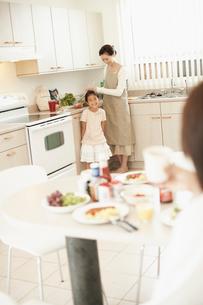 食卓のお父さんとママを手伝う女の子の写真素材 [FYI02061376]