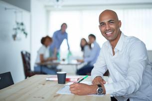 仕事をする外国人男性とミーティングをする同僚たちの写真素材 [FYI02061438]