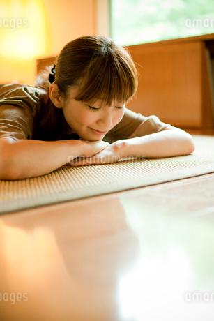 床に寝転ぶ女性の写真素材 [FYI02061463]