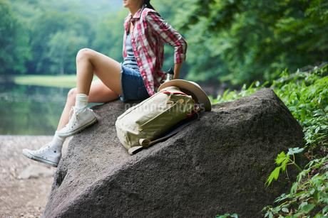 岩の上に座る女性とリュックサックの写真素材 [FYI02061497]