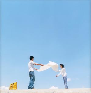 レジャーシートを広げるカップルと大空の写真素材 [FYI02061599]