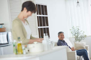 料理をするシニア女性とリビングでくつろぐシニア男性の写真素材 [FYI02061638]