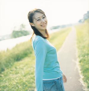 土手の小道を歩きながら振り向く女性の写真素材 [FYI02061656]