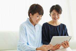 タブレットPCを見る女性2人の写真素材 [FYI02061691]