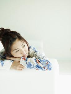 ソファに横になりくつろぐ若者女性の写真素材 [FYI02061709]