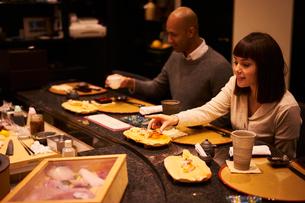 寿司屋で食事をする外国人カップルの写真素材 [FYI02061719]