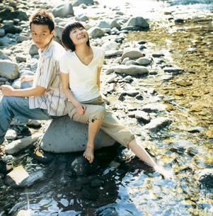 川の水に足を入れるカップルの写真素材 [FYI02061733]