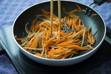 フライパンで炒めるニンジンとゴボウの写真素材 [FYI02061751]