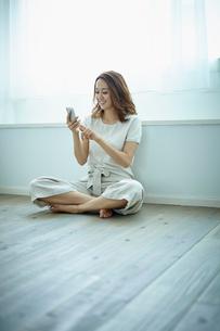 窓辺に座りスマートフォンを操作する女性の写真素材 [FYI02061757]