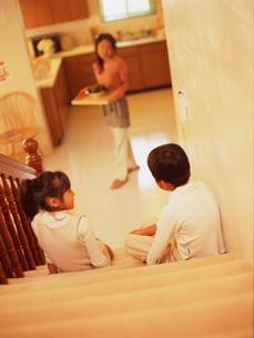 キッチンのお母さんと階段に座る子供の写真素材 [FYI02061842]
