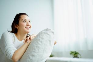 クッションにもたれてくつろぐ笑顔の女性の写真素材 [FYI02061907]