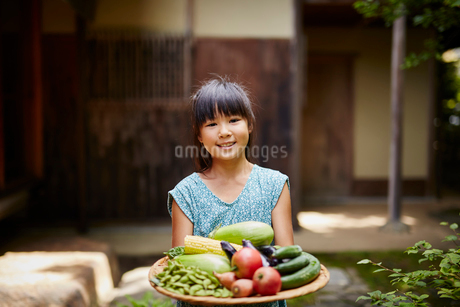 夏野菜を持つ女の子の写真素材 [FYI02061930]