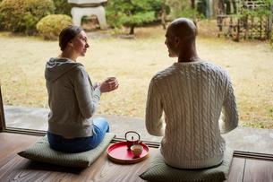縁側でお茶を楽しむ外国人カップルの写真素材 [FYI02061933]