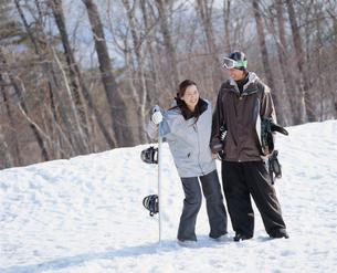 雪の上に寄り添って立つスノーボーダーカップルの写真素材 [FYI02061995]