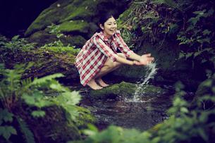 清流で水遊びをする女性の写真素材 [FYI02062008]