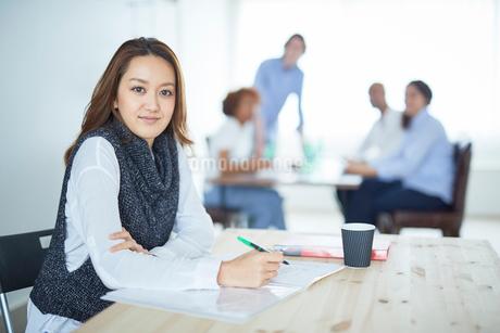 仕事をする日本人女性とミーティングをする同僚たちの写真素材 [FYI02062052]
