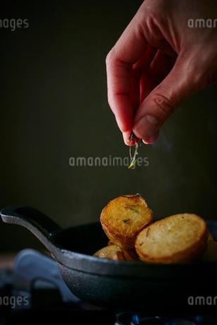 ジャガイモにローズマリーをかける女性の手元の写真素材 [FYI02062069]