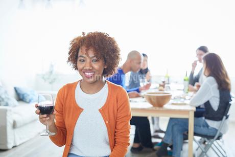 赤ワインを持つ外国人女性と食事をする仲間たちの写真素材 [FYI02062090]