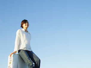 スーツケースに座るジーンズの女性と空の写真素材 [FYI02062102]