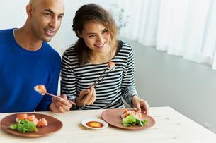 カリフォルニアロールを食べる外国人カップルの写真素材 [FYI02062180]
