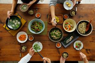 和食がのった食卓と食事をする4人の手元の写真素材 [FYI02062183]