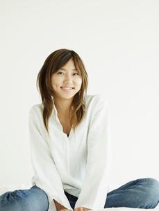 白い壁の前のジーンズの女性の写真素材 [FYI02062201]