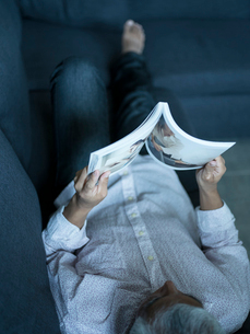 ソファに寝転び本を読むシニア男性の写真素材 [FYI02062202]