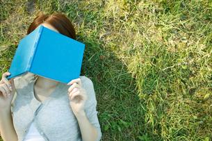芝生の上で本を顔にのせ休む女性の写真素材 [FYI02062203]